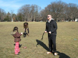 A puppy named Stella, a pit bull & lab mix, off-leash finds a friendly human to greet