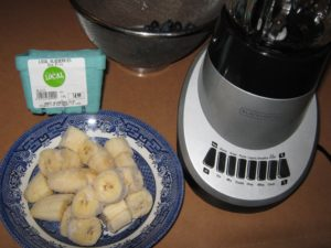 Frozen banana pieces, blueberries and unfancy Black and Decker blender ready to use