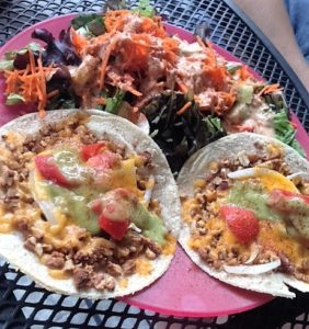 Maggie's Nut Meat Tacos, made with farmstead cheddar, tomatoes, onions and topped with an avocado cream sauce & served with a delicious green salad