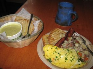 """Veggie omelette with spinach, caramelized onion, grated carrot, avocado & cheddar cheese served with hoe fries and toast plus side order of bacon"